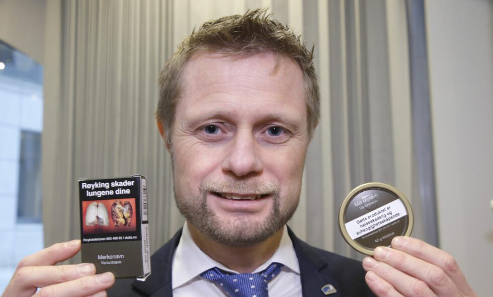 TOBAKKSREKLAME: Helse- og omsorgsminister Bent Høie (H) med nye og standardiserte tobakkspakker. Foto: Vidar Ruud / NTB Scanpix