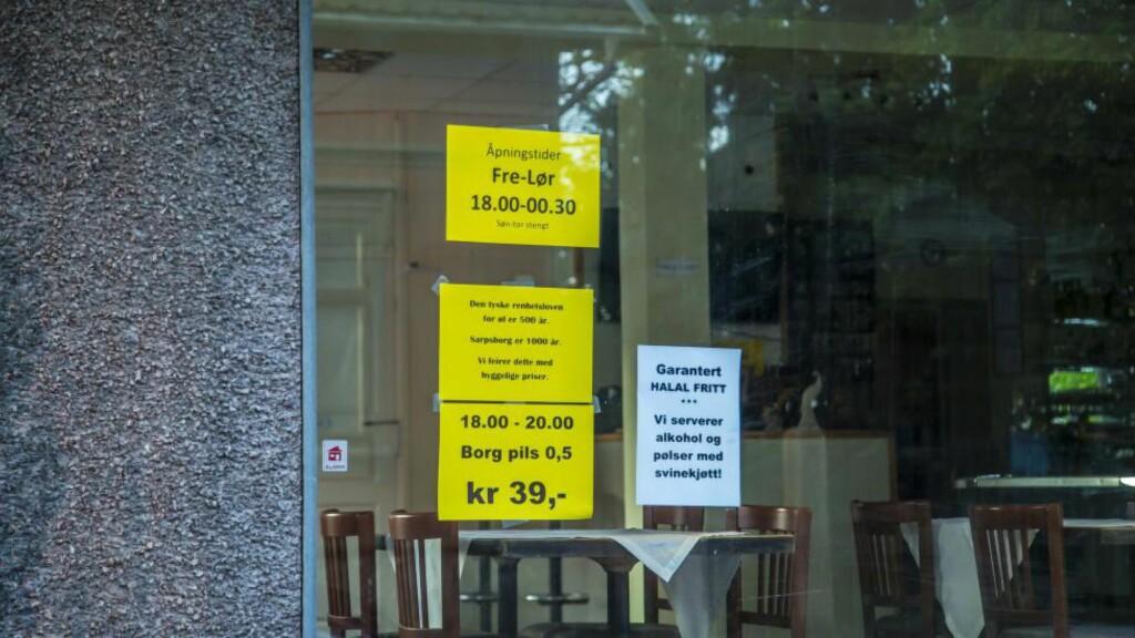 «HALAL-FRITT»: Naboen til denne puben i Sarpsborg er den somaliske moskeen i byen. Her reklamerer pubeieren for garantert «halalfritt». Både plakaten og ølreklamen ved siden av, kan føre til at pubeieren mister skjenkebevillingen. Foto: Vetle Granath Magelssen