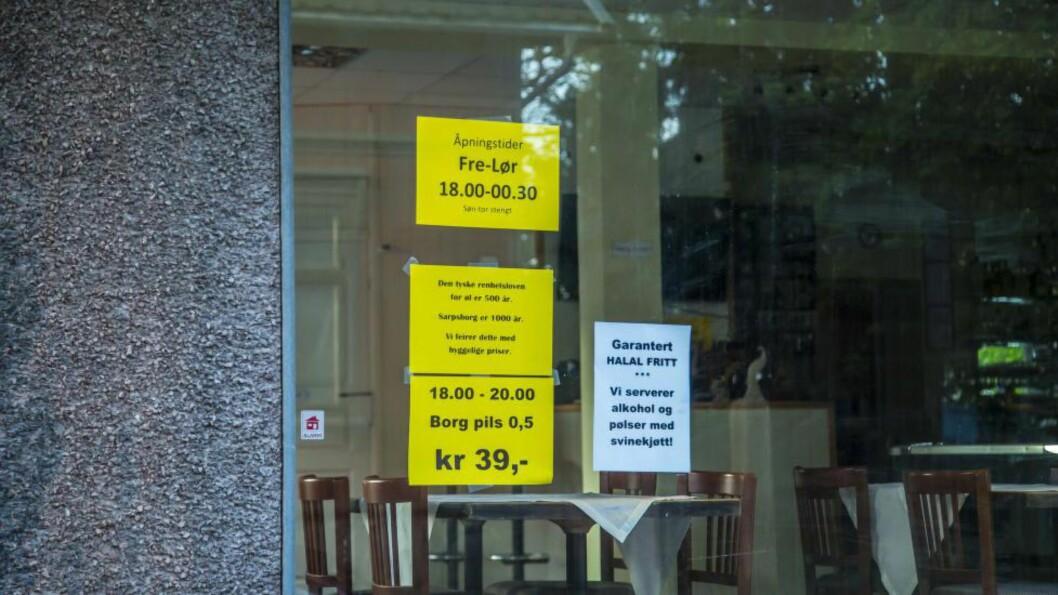 <strong>«HALAL-FRITT»:</strong> Naboen til denne puben i Sarpsborg er den somaliske moskeen i byen. Her reklamerer pubeieren for garantert «halalfritt». Både plakaten og ølreklamen ved siden av, kan føre til at pubeieren mister skjenkebevillingen. Foto: Vetle Granath Magelssen