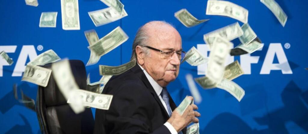 PENGENE SATT LØST:  Da FIFAs president Joseph Blatter skulle holde sin pressekonferanse i forbindelse med det ekstraordinære møtet i FIFA-komiteen i Zürich i juli, kastet den britiske stuntkomikeren Simon Brodkin penger på Blatter. Et bilde som betegnet situasjonen i FIFA. Foto: EPA / NTB Scanpix