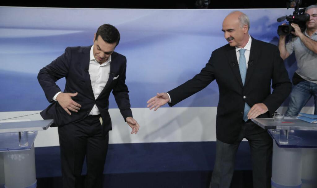 KRISEVALG: Avgått statsminister Alexis Tsipras fra Syriza henger fast i en mikrofon-ledning idet han skal hilse på utfordreren Evangelos Meimarakis fra Nytt Demokrati under en debatt i fjernsyn, som foregikk i svært så høvelige former. På meningsmålingene er det dødt løp. Foto: AP / Scanpix / Lefteris Pitarakis
