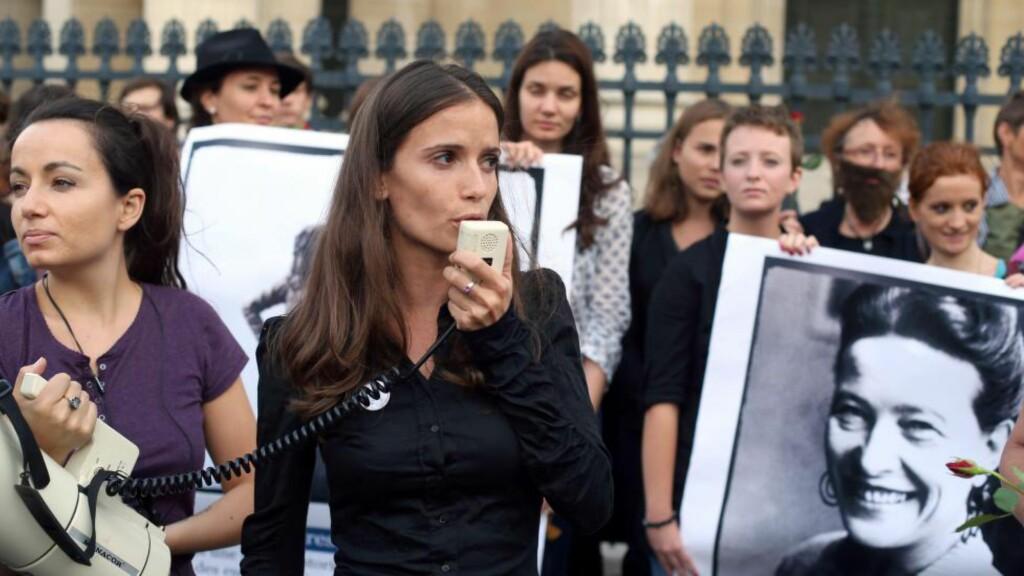 """FEMINIST FORDI: - Det er når summen av maktkritisk satire sjølv blir ein maktfaktor. Det er når summen av kanskje hyggelege, kanskje kjipe, seksuelle tilnærmingar gjer at ho føler at ho må bruke tida si på å vere eit seksuelt vesen, skriver artikkelforfatteren. Bildet er av den franske, feministiske organisasjonen """"Osez le feminism"""" (Våg feminisme) og en plakat av feministen Simone De Beauvoir. Foto: NTB Scanpix."""