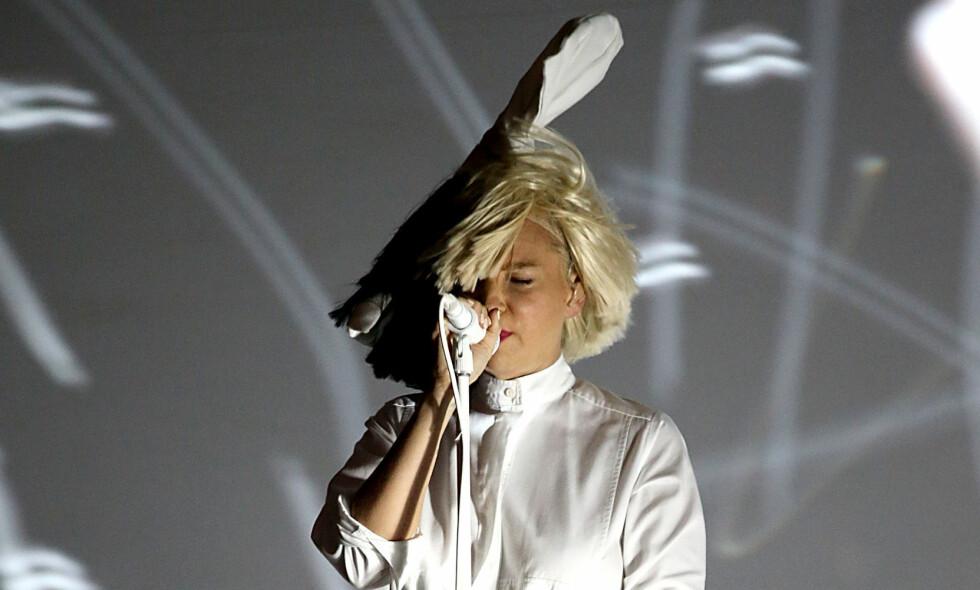 LUFTIG ØYEBLIKK: Sia har gjort det til et varemerke å skjule fjeset bak tunge parykker. Men under en konsert i Colorado i forrige uke var rett og slett ikke panneluggen tung nok da vinden tok tak. Dermed endte den anonymitetselskende artisten opp med ufrivillig å vise ansiktet. Foto: Getty Images