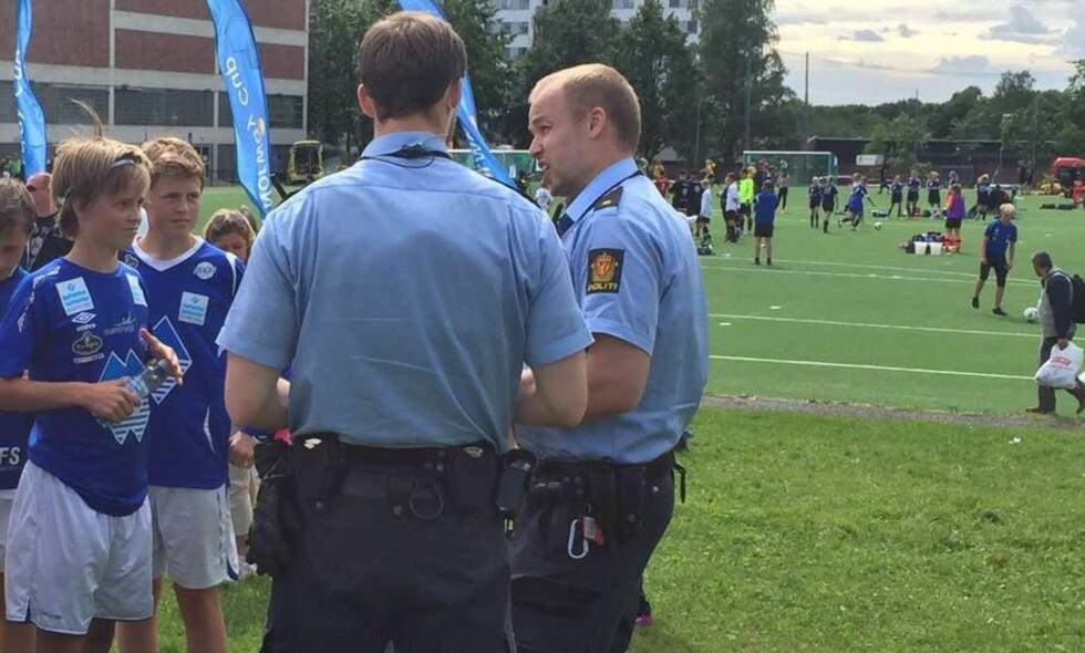 SNAKKET OM SITUASJONENEN: Politiet kom til banen etter de to lagene hadde gått hvert til sitt. Her snakker de med Herd-spillerne Ola (t.v) og Magnus. Magnus var på kampen for å se på lagkameratene. Foto: Herd