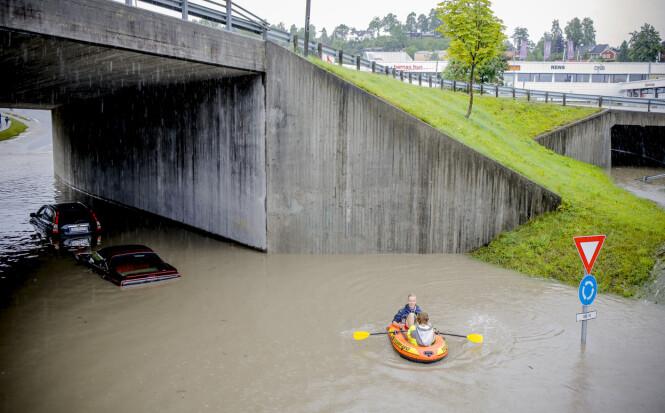 <strong>BÅT PÅ VEIEN:</strong> På Fekjan ved Holmen i Asker står biler under vann, og folk har tatt til årene. Foto: Krister Sørbø / NTB Scanpix