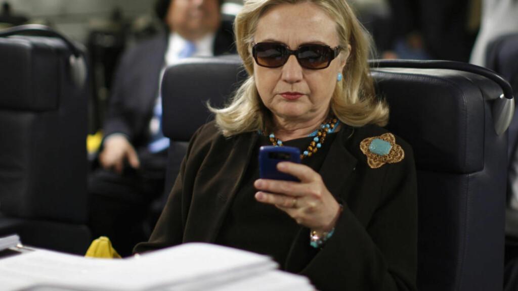 ETTERFORSKES: Hillary Rodham Clinton sjekker telefonen under en tur til Libya i 2011 mens hun var utenriksminister. Foto: AP Photo/Kevin Lamarque, Pool, File