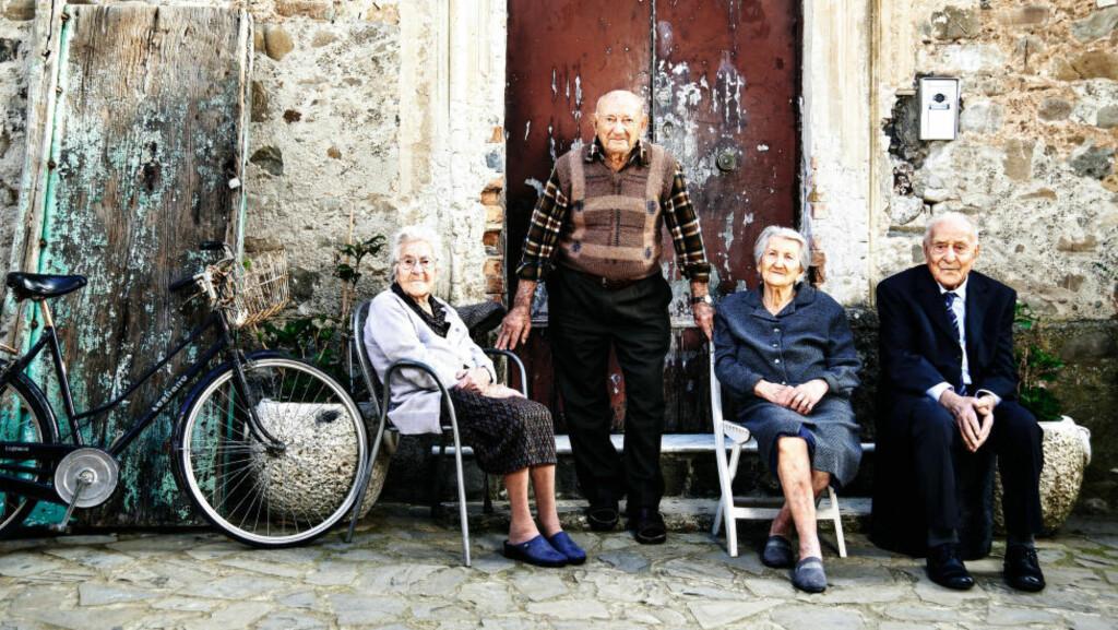 DE GAMLE HAR DET GODT: I den italienske kystbyen Acciaroli blir innbyggerne så gamle at forskerne nå vil finne ut hva hemmeligheten er. Og de lever det gode liv. Fra venstre: Michelina Valsallo (97), Giuseppe Valsallo (94), Amina Valsallo (93) og  Antonio Valsallo (100). Antonio og Amina er gift. Michelina er Antonio's søster, mens Giuseppe er fetteren. Foto: Tom Jackson / The Times