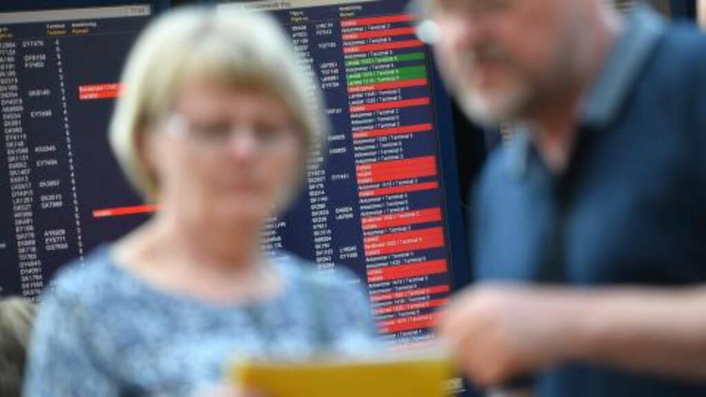 PÅ BAKKEN: passasjerer ved Arlanda-flyplassen i Stockholm foran en lystavle med kansellerte avganger. En svikt i datasystemene førte til at alle fly rundt Stockholm og Göteborg ble tvunget på bakken i ettermiddag. Foto: EPA/JOHAN NILSSON / TT SWEDEN OUT