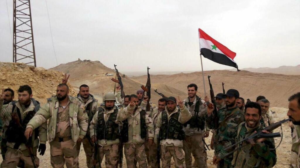 FEIRER: Syrisk regjeringsstyrker viser seierstegnet i utkanten av den historiske byen Palmyra, på dette bildet fra det syriske nyhetsbyrået SANA. Nyhetsbyrået Reuters, som har distribuert bildet, tar forbehold om autentisiteten.