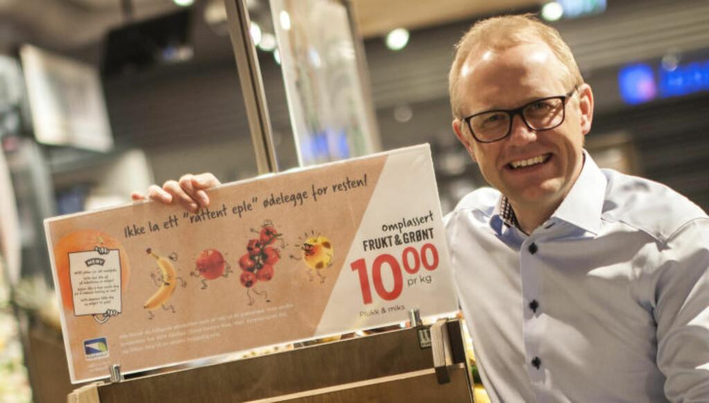 OMPLASSERT: Driftssjef i Meny, Espen Tollefsen, med skiltet du skal se etter om du vil kjøpe overskuddsfrukt- og grønt. Foto: MENY