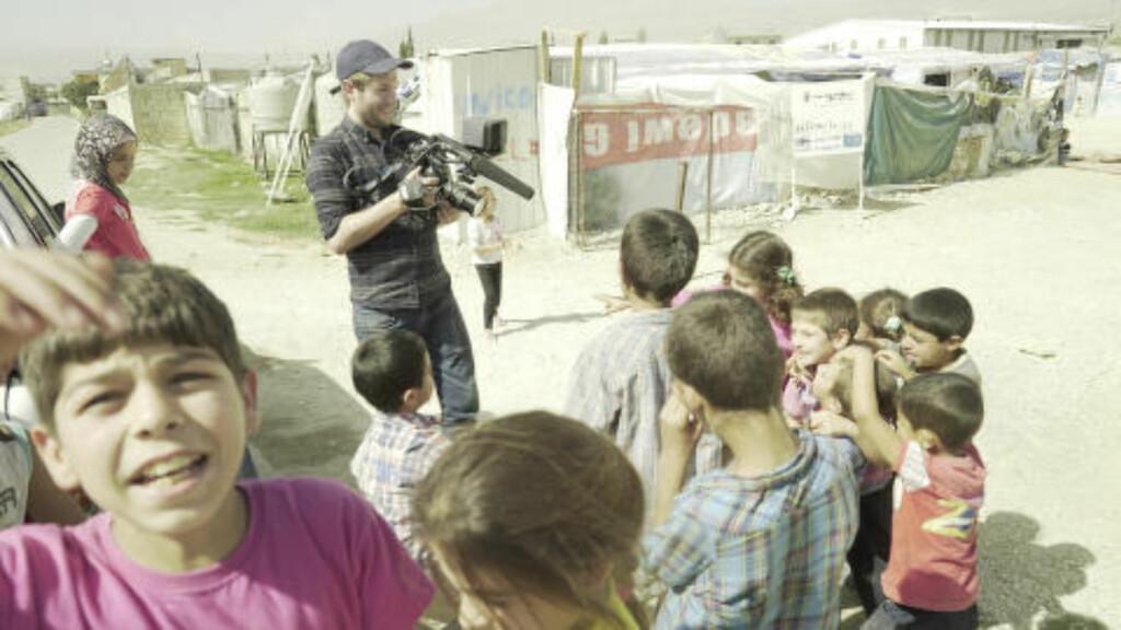 I FLYKTNINGLEIR: Regissør for dokumentaren, Peder Borch Gieæver, står her med barna i en av flyktningleirene teamet besøkte. Foto: Novemberfilm