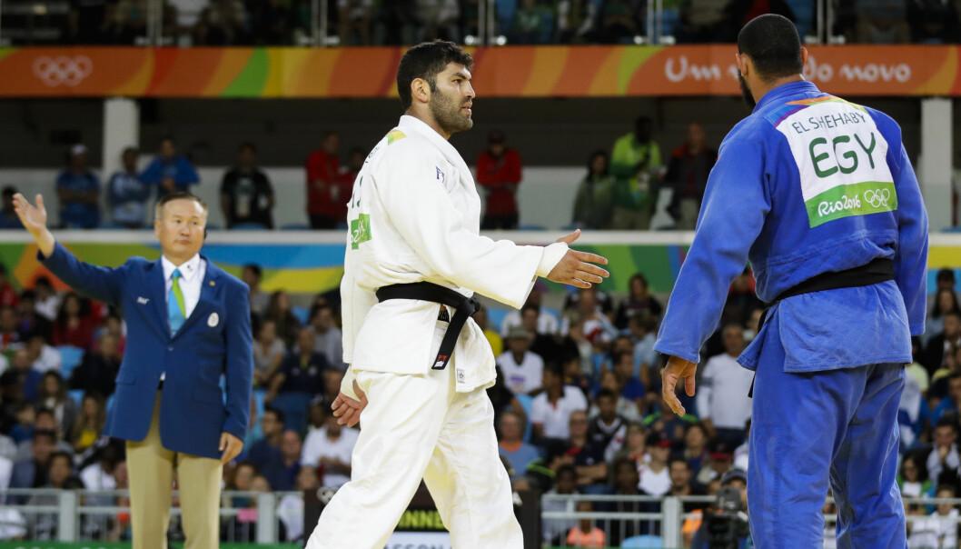 <strong>FIKK KRITIKK:</strong> Egypts Islam El Shehaby (i blått) nektet å ta Israels Or Sasson i hånden. Nå er han sendt hjem. Foto: AP Photo/Markus Schreiber/NTB Scanpix