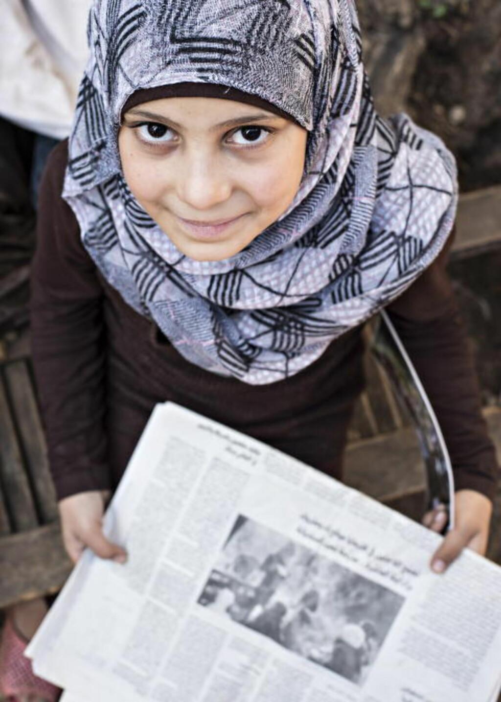 STOLT:  Baraa (10) viser stolt fram avisa som skrev om henne for tre år siden, da Baraa (den gang sju år) startet skole for sine medflyktning-barn, under et tre.    Foto: Hans Arne Vedlog / Dagbladet