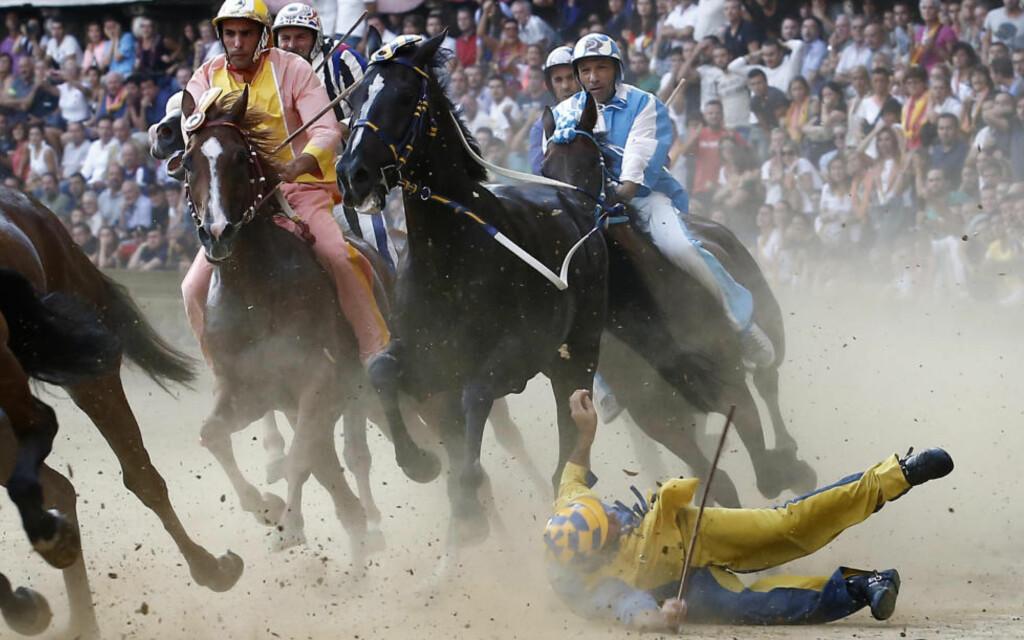 EKSTREMT: En rytter faller av hesten under det andre av de to årlige Palio de Siena-hesteløpene i Toscana, Italia. Løpet er tema for en ny film av Cosima Spender, og avslører både korrupsjon og intriger av uante dimensjoner. Foto: AP Photo/Paolo Lazzeroni
