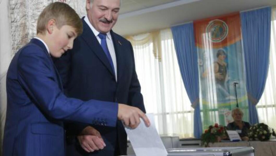 SÅNN SKAL DET GJØRES: Pappa Aleksandr Lukasjenko lar sønnen Nikolai slippe stemmeseddelen i urnen under gårsdagens presidentvalg. Foto: AP Photo/Sergei Grits/NTB Scanpix