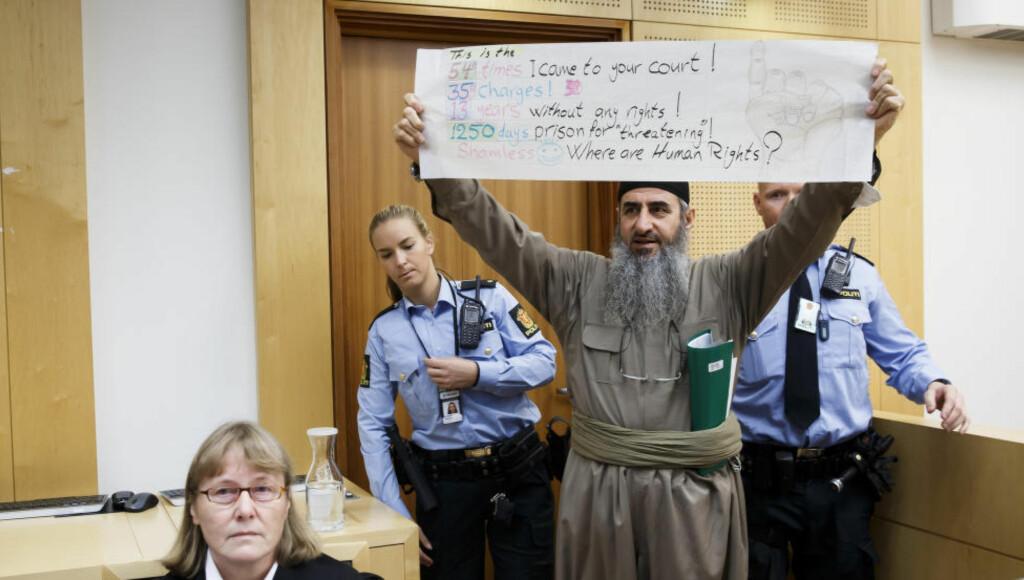 VISTE PLAKAT: Mulla Krekar viser fram plakat i retten. Foto: Heiko Junge / NTB scanpix