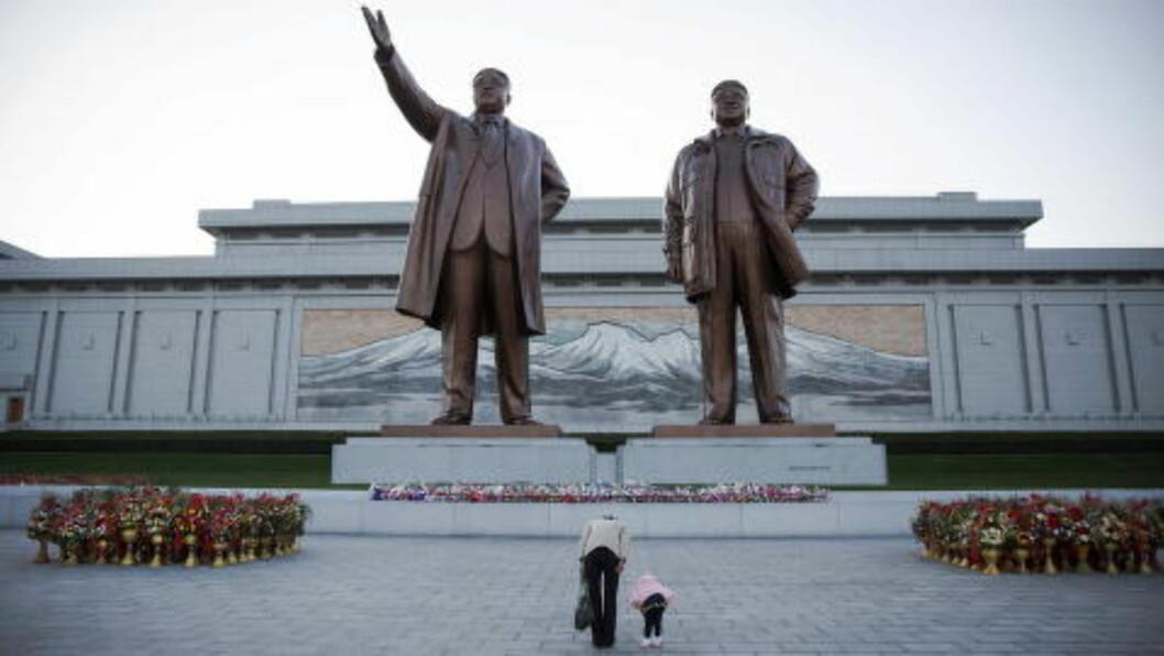 NESEGRUS BEUNDRING:  En kvinne og hennes lille datter bukker dypt for statuen av Kim Il Sung (den første) og Kim Jong Il (den andre) under 70-årsferiingen for det nordkoreanske kommunistpartiet søndag. Foto: Damir Sagolj, Reuters/NTB Scanpix.