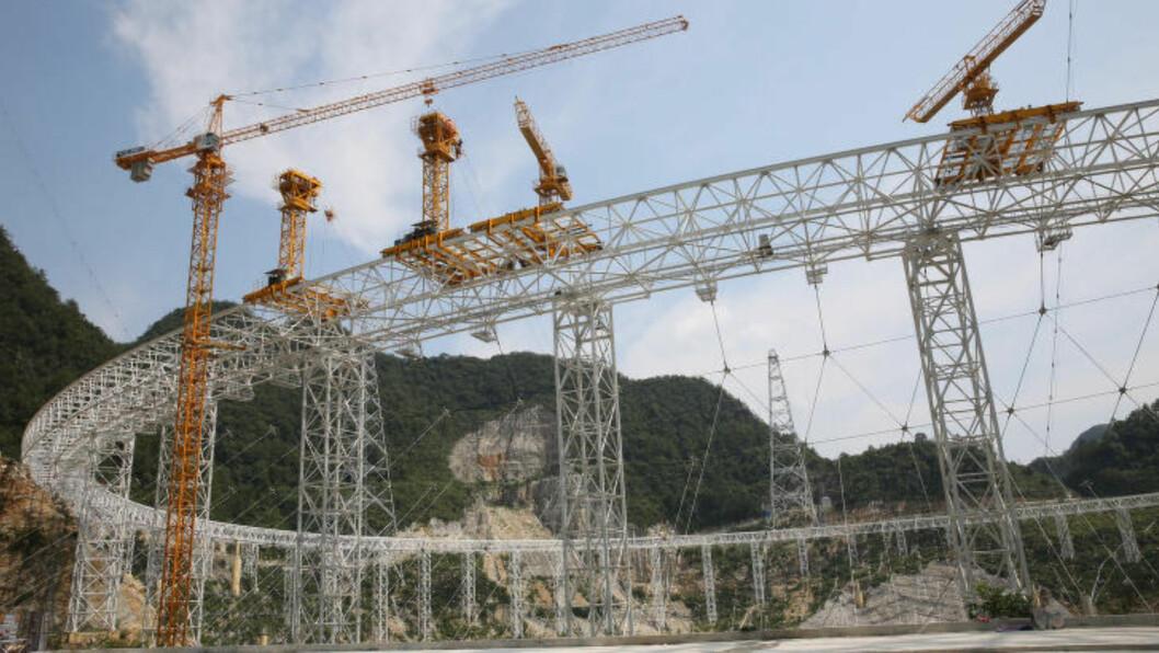 <strong>UNIK STRUKTUR:</strong> I stedet for å være plassert over bakken, er teleskopet er bygd på pillarer i et naturlig søkk i terrenget. Dette, kombinert med geografien i området og den avsidesliggende plasseringen i Guizhou-provinsen, gjør at forstyrrende radiostøy fra vår egen planet vil reduseres. Foto: Xinhua / Sipa / Retuers / NTB Scanpix