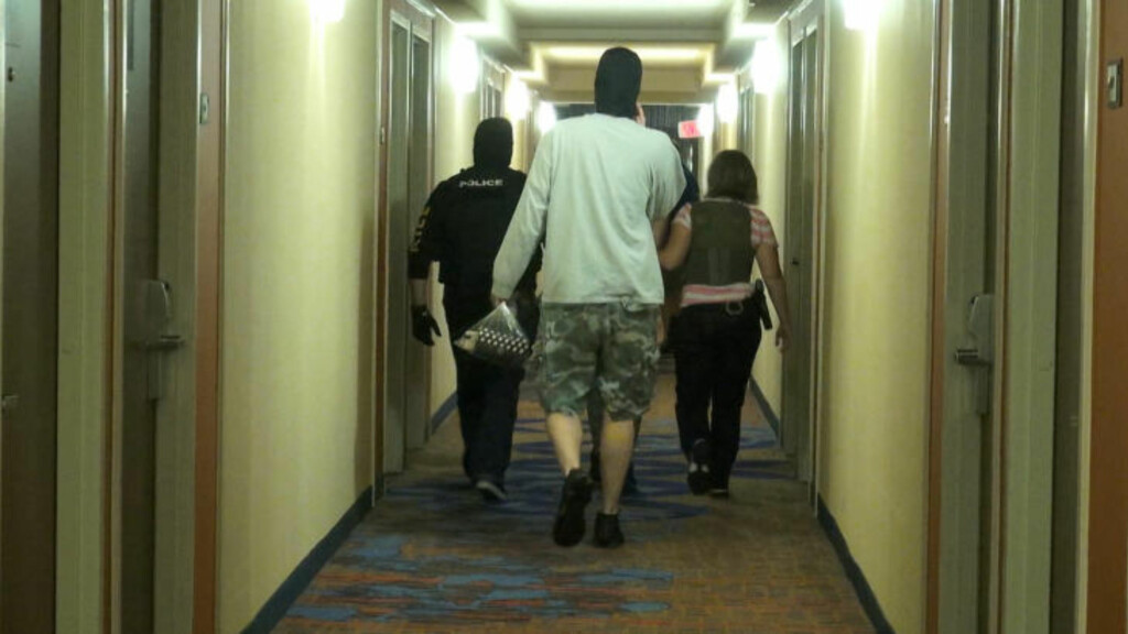 ARRESTERT: En av rundt 150 personer ble arrestert forrige uke ledes ned en hotellgang etter at rundt 500 politi- og FBI-betjenter slo til mot menneskehandel over hele USA. Foto: FBI