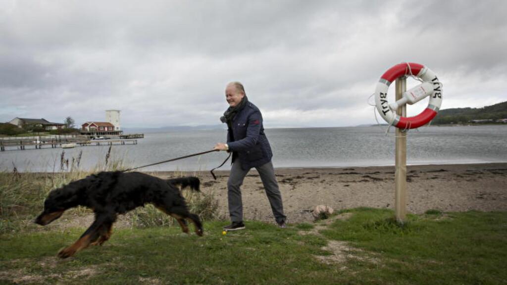 UNDER ÉN MÅNED IGJEN: Per-Mathias Høgmo - og hunden hans, Figo - fulgte trekningen fra sofaen hjemme på Jeløya. Nå begynner arbeidet med å finsikte motstanderen. Foto: Anita Arntzen