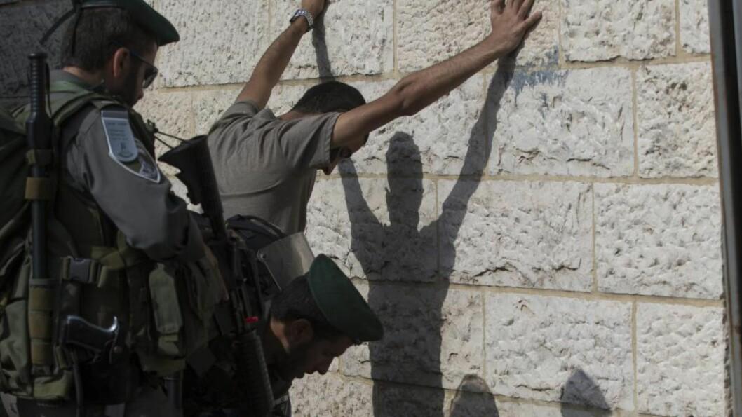 VIL GJØRE DET ENKLERE Å RANSAKE: Politimenn ransaker en palestinsk mann i gamlebyen i Jerusalem. Regjeringens nye lovforslag vil gjøre det mulig for politiet å kroppsvisitere personer uten begreunnelse. Foto: EPA/ATEF SAFADI