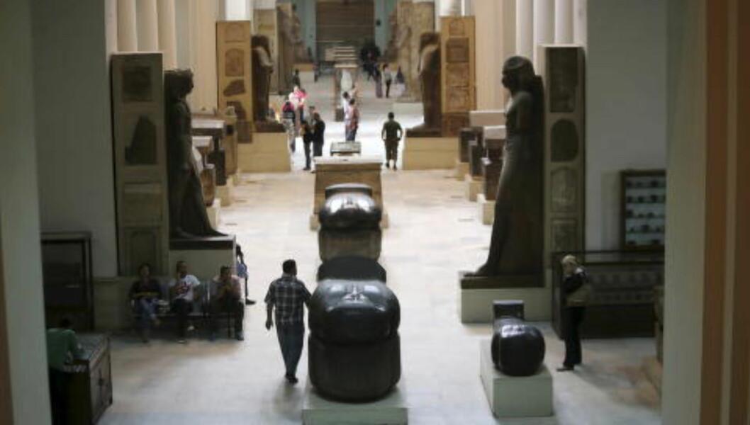 STEINSKULPTURER: Turister ser på gjenstandene som er utstilt i det egyptiske museet. På dette blidet kan man se flere sarkofager og statuer, alle sammen av stein. Foto: REUTERS / Mohamed Abd El Ghany