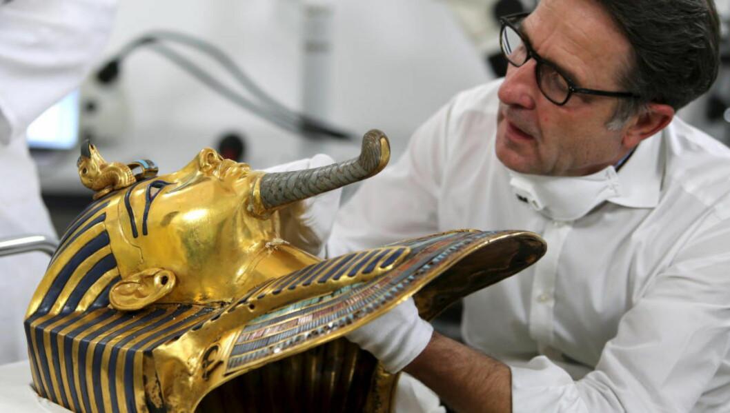 OMSTENDELIG: Den tyske konservatoren Christian Eckmann viser frem Tutankhamons maske, og hvordan man har tenkt til å restaurere den. Foto: REUTERS / Mohamed Abd El Ghany.