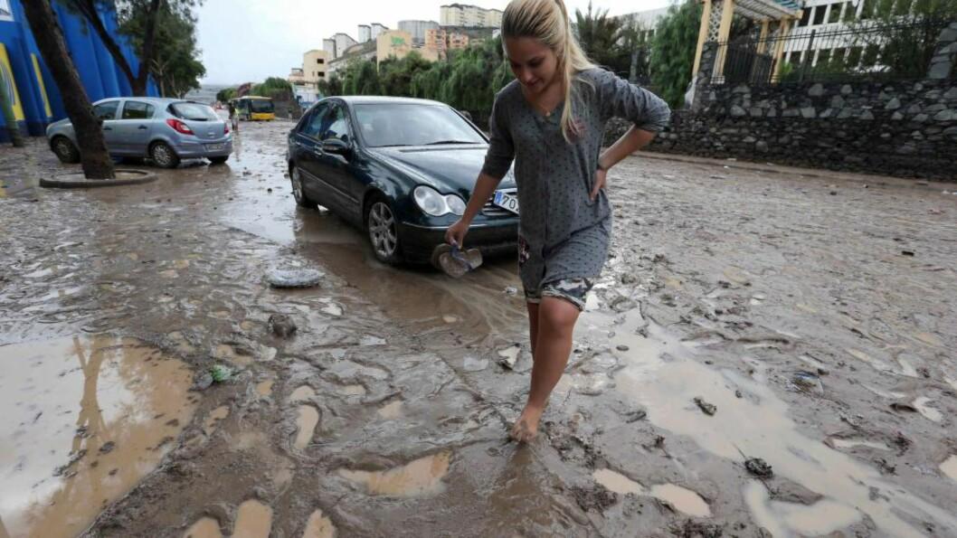 GJØRME:  En kvinne passerer en gjørmete gate i Las Palmas på Gran Canaria.  Foto: EPA/ELVIRA URQUIJO A.