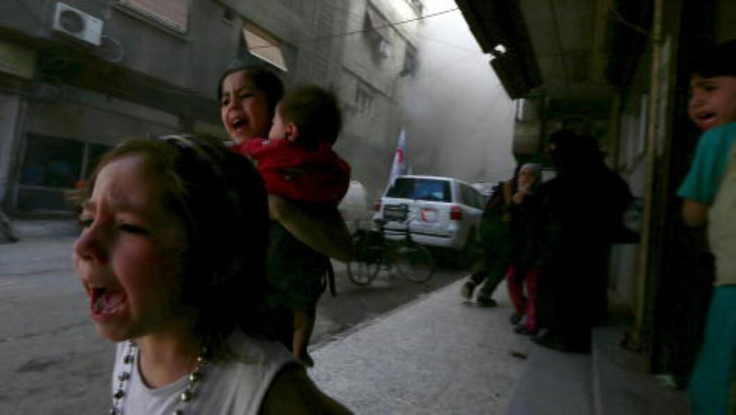 ENORM FRYKT:  Jenta Ghazal (4), sjuårige Judy og den åtte måneder gamle Suhair løper redde i gatene i et bombeangrep utført av den syriske regjeringshæren i nabolaget Douma, ved Damaskus. Fem år etter revolusjonsstarten i Midtøsten, er situasjonen spesielt vanskelig for syrerne. Foto: Bassam Khabieh / Reuters / Scanpix