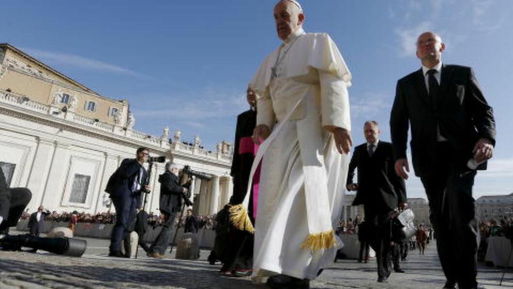 AVSLØRINGER:  Vatikanet får skyllebøtter av negativ oppmerkomshet i to nye bøker basert på lekkasjer fra den katolske kirkes indtre sirkler. Her pave Frans sammen med en sikkerhetsvakt på sin ukentlige prosesjon onsdag på Petersplassen. Foto: Alessandro Bianchi, Reuters/NTB Scanpix.
