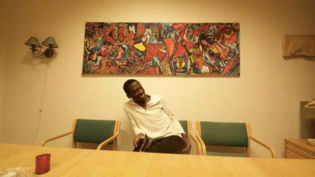SMILER: Abdilatifu Ssenyondwa smiler fra øre til øre. Her i SEIFs lokaler har han tilbrakt mye tid. Nå håper han på å kunne skaffe seg en jobb. Foto: Ådne Husby Sandnes