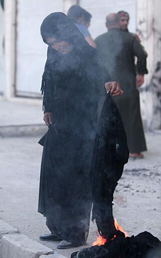 BRANT NIKAB: En kvinne satte fyr på en nikab i etterkant av IS-tilbaketoget fra Manbij. Foto: REUTERS/Rodi Said