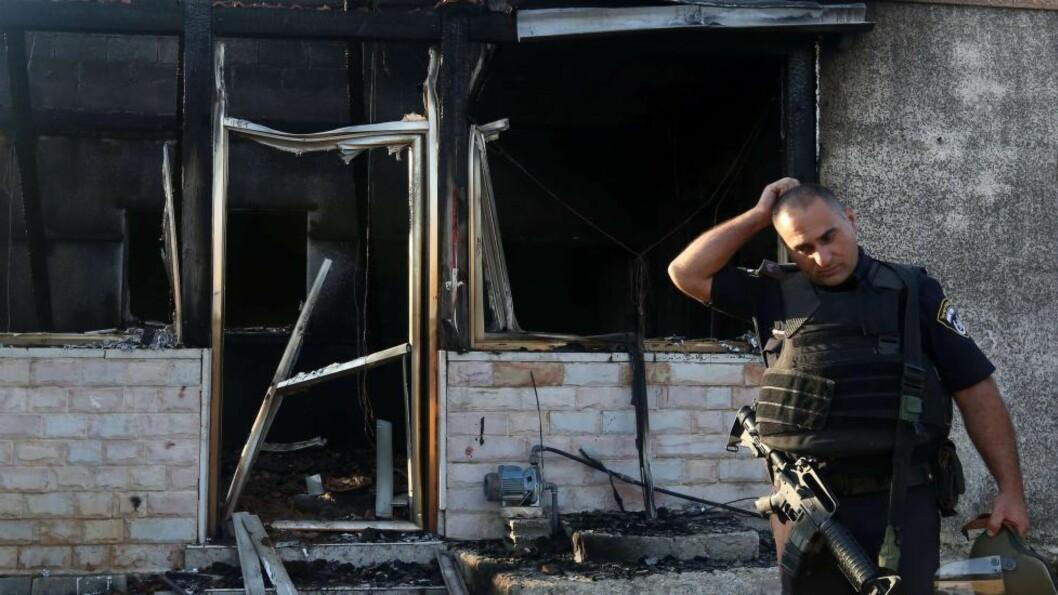 <strong> MORDBRANN:</strong>  En mann fra den israelske sikkerhetsstyrken foran et av husene som ble påtent i landsbyen Doma på Vestbredden tidlig fredag morgen. Israelske myndigheter kalte umiddelbart brannstifterne for terrorister. Også Israels ambassadør til Norge fordømmer handlingen på det sterkeste. Foto:  JAAFAR ASHTIYEH, AFP/NTB Scanpix.