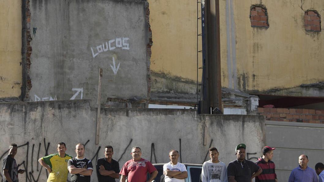 <strong>VED ÅSTEDET:</strong> Alvoret står skrevet i ansiktene til disse mennene i Sao Paulo-forstaden Osasco, på et fotografi tatt forrige fredag. På motsatt side av gata ligger baren hvor minst 10 mennesker ble skutt kvelden i forveien, av maskerte drapsmenn som mistenkes å være politifolk. Drapsmennene steg ut av en bil og begynte å skyte. Foto: AP/Andre Penner