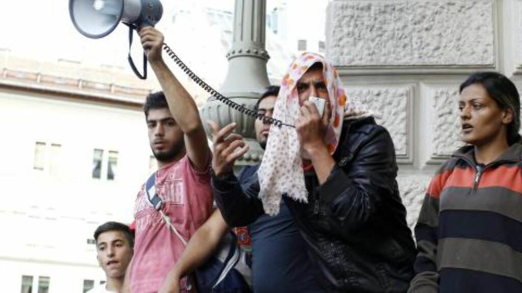 PROTESTERER: Mange har gyldige togbilletter de kjøpte ved ankomst i Ungarn, men likevel får de ikke reise videre. Samtidig som det pågår store protester ved jernbanestasjonen Keleti i Budapest, har hundrevis av migranter og flyktninger begynt å gå til fots mot Østerrike. Foto: EPA/ZSOLT SZIGETVARY HUNGARY OUT/NTB Scanpix