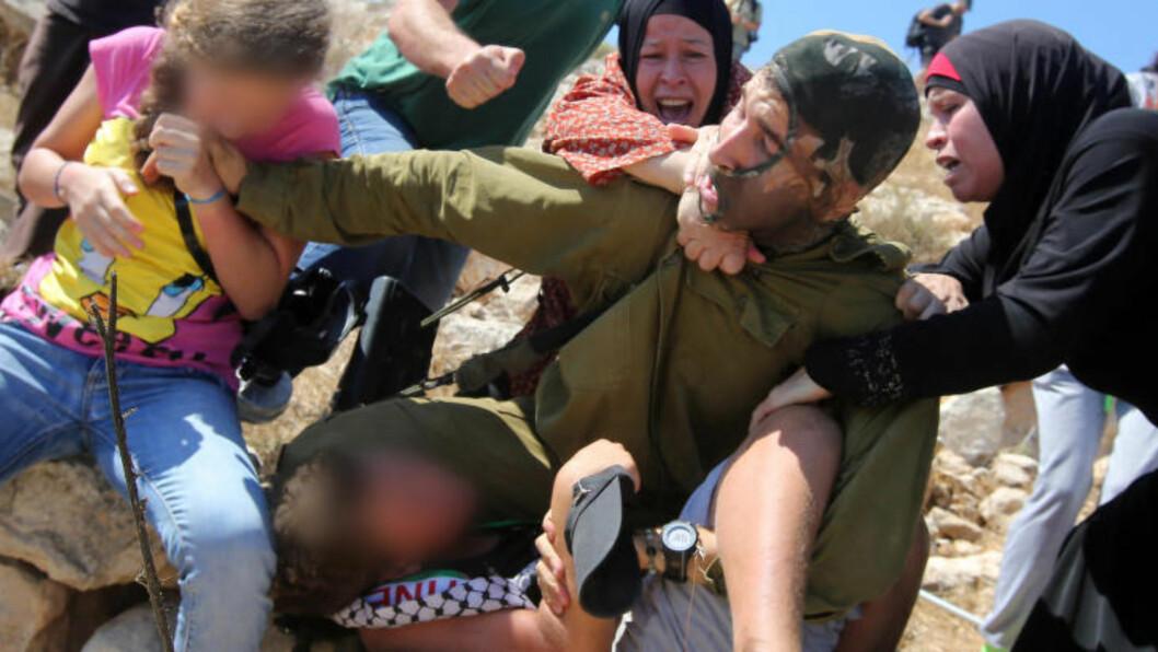 <strong>FAMILIEN GREP INN:</strong> Guttens mor og søster var blant personene som gikk løs på soldaten, som skal ha forsøkt å arrestere ham. Foto: ABBAS MOMANI / AFP / NTB SCANPIX