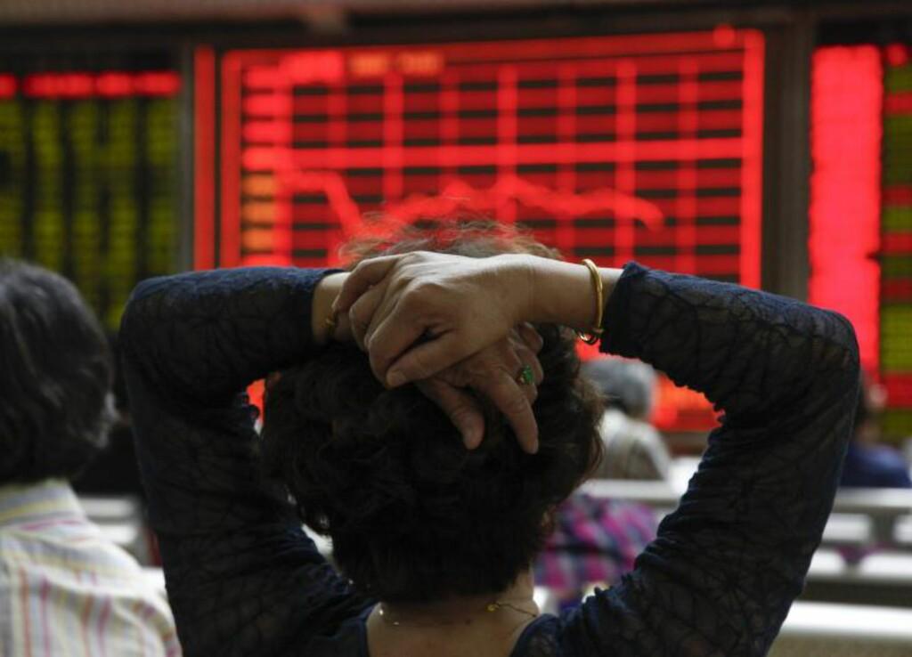 NED I DAG: En investor følger med på kursene ved et meglerhus i beijing i dag. Kinesiske børser gikk nedover for andre dag på rad i dag etter flere dager med oppgang i slutten av august. Foto: ROLEX DELA PENA /  EPA / NTB SCANPIX