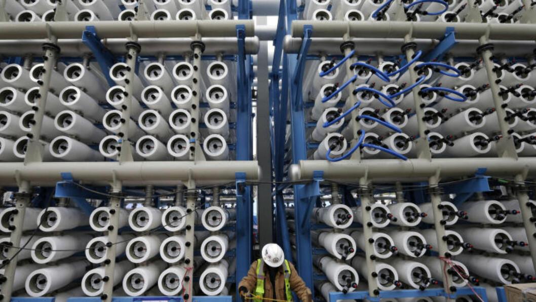 <strong>AVSALTER SJØVANN:</strong> En arbeider står mellom omlag 2 000 trykkbeholdere, som skal avsalte sjøvann og gjøre det drikkbart. Dette avsaltingsanlegget i Carlsbad skal åpne sent i 2015. Foto: AP Photo/Gregory Bull/NTB Scanpix