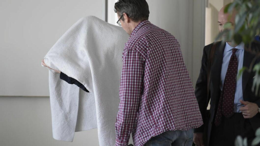 <strong>SKJULTE ANSIKTET:</strong> Den siktede statsadvokaten skjulte ansiktet med et håndkle da han ankom rettslokalet  i dag. Foto: Ulf Palm / TT / NTB Scanpix