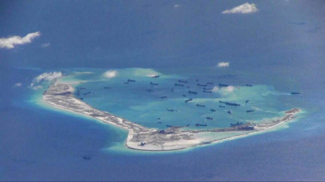 <strong>KUNSTIG ØY:</strong> Dette bildet viser hvordan kinesiske mudderprammer pumper opp store mengder sand og bygger en kunstig øy over korallrevet Mischief Reef i Sør-Kinahavet. Foto: U.S. Navy/Reuters/Scanpix