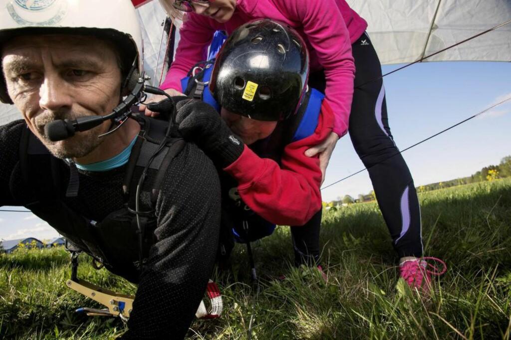 GODE HJELPERE: Jan er, med god hjelp fra Hege Berntsen, klar for en luftetur på ryggen til tandempilot Reidar Berntsen. Foto: LARS MYHREN HOLAND
