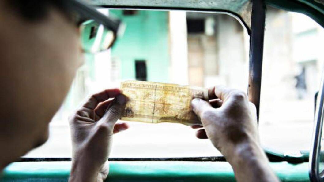 <strong>GODE PENGER:</strong> Hver passasjer betaler 10 pesos cubanos, cirka tre-fire kroner. Det blir en del penger i løpet av en dag. Her sjekker sjåføren at seddelen er ekte. Foto: NINA HANSEN