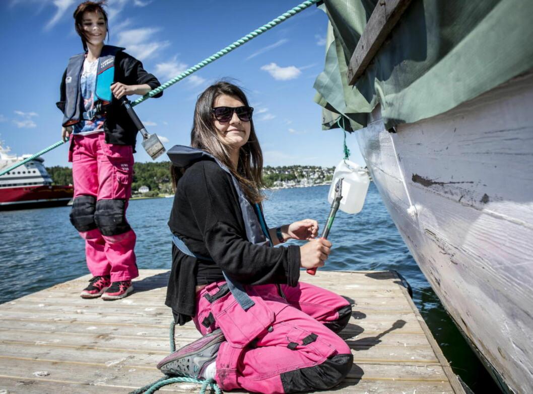 <strong>FYSISK ARBEID:</strong>  Shqipone «Skippy» Kastrati (t.h.) og Tina Korovic er på Nav-tiltak. De har fått jobben med å skrape  maling av en gammel losbåt. Foto: Øistein Norum Monsen