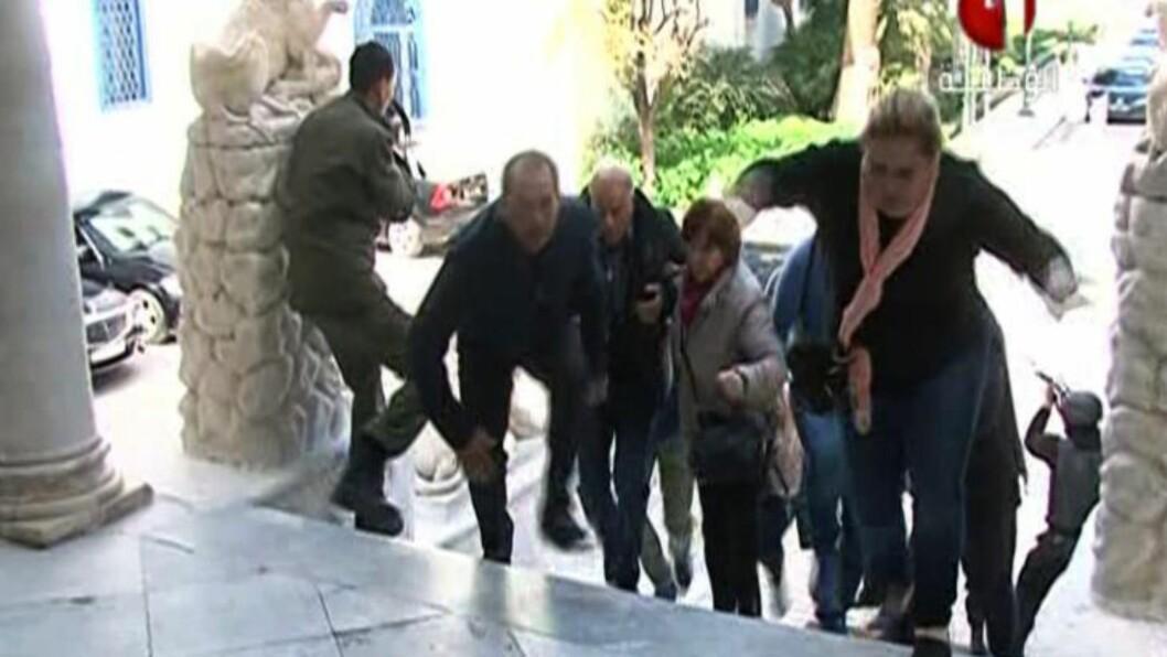 TOK GISLER: Et bilde tatt fra Tunisisk statlig TV viser gisler som rømmer fra bardo-museet , det to angripere drepte turister og tok gisler i dag. Foto: AFP PHOTO / TUNISIA 1