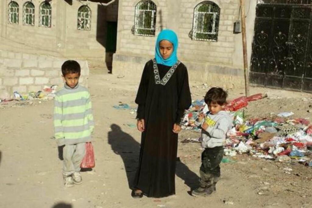 SAVNER NORGE:  Suleiman (6), Shaimaa (11) og lillebroen Haron (3) utenfor nabolaget der de nå bor i Sanaa, i hovedstaden Jemen. For to dager siden ble over 140 mennesker drept i angrep begått av terrorgruppa IS i Sanaa, og eksperter frykter at landet er på vei inn i full borgerkrig. Foto: Privat