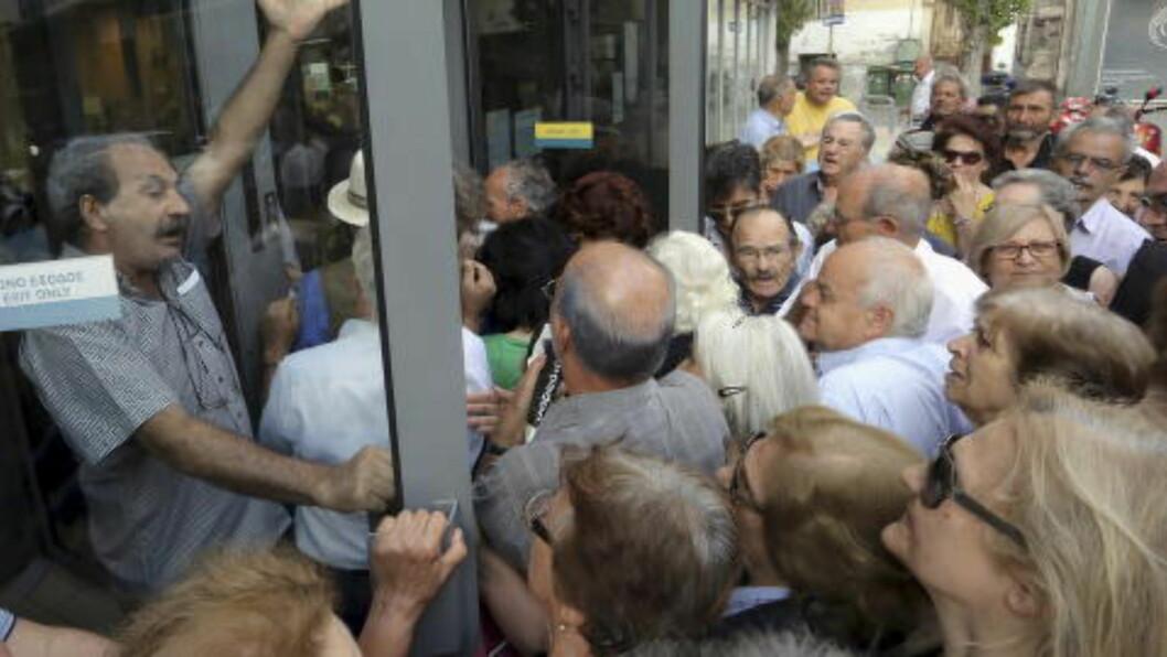 <strong>RASER I BANKENE:</strong> Her står pensjonister i kø for å få ut deler av pensjonen sin. Køene er lange, og pensjonistene i Hellas er frustrerte. Foto: Stefanos Rapanis / Reuters