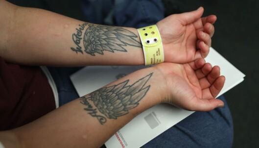 KVINNELIG FANGE: En kvinnelig innsatt i et fengsel i Connecticut, USA, viser fram totoveringene sine. Foto: John Moore/Getty Images/AFP