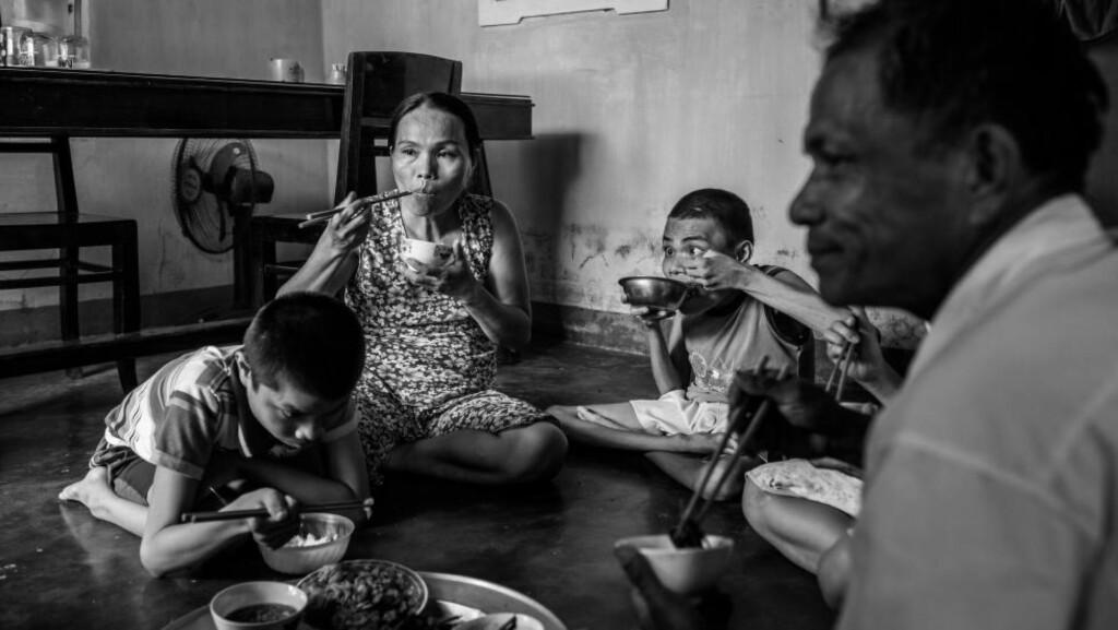 HARD HVERDAG: Brødrene Tri (16) og Hau (15) er helt avhengige av foreldrene Nham og Dong. Familien får ca. 500 kroner i måneden i støtte fra myndighetene for å få hverdagen til å gå opp. Foto: Quinn Ryan Mattingly