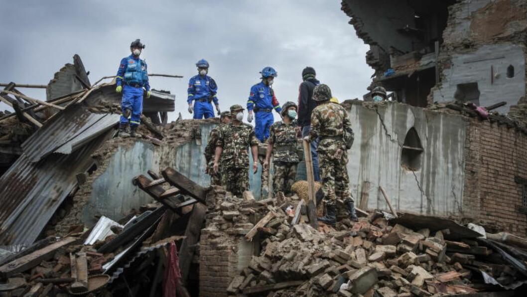 <strong>LETER:</strong> En rekke utenlandske redningsarbeidere har kommet til Nepal etter jordskjelvet. Her leter et kinesisk team etter ei begravd død jente i byen Sako, sammen med det nepalske militæret.  Foto: Øistein Norum Monsen / Dagbladet
