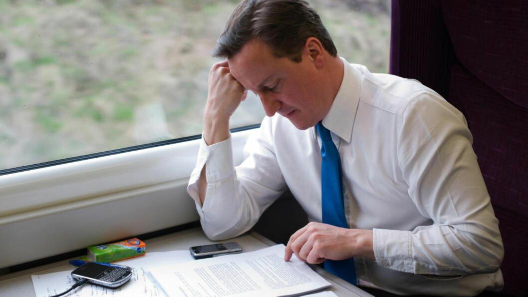 PHONY: Storbritannias statsminister David Cameron har knapt blitt sett med mobiltelefon offentlig etter han ble statsminister i 2010. Her sitter han imidlertid på toget på vei til Leeds under valgkampen i 2010 med hele to telefoner. I dag ble han tulleringt. Foto: REUTERS/Leon Neal/Pool/NTB Scanpix